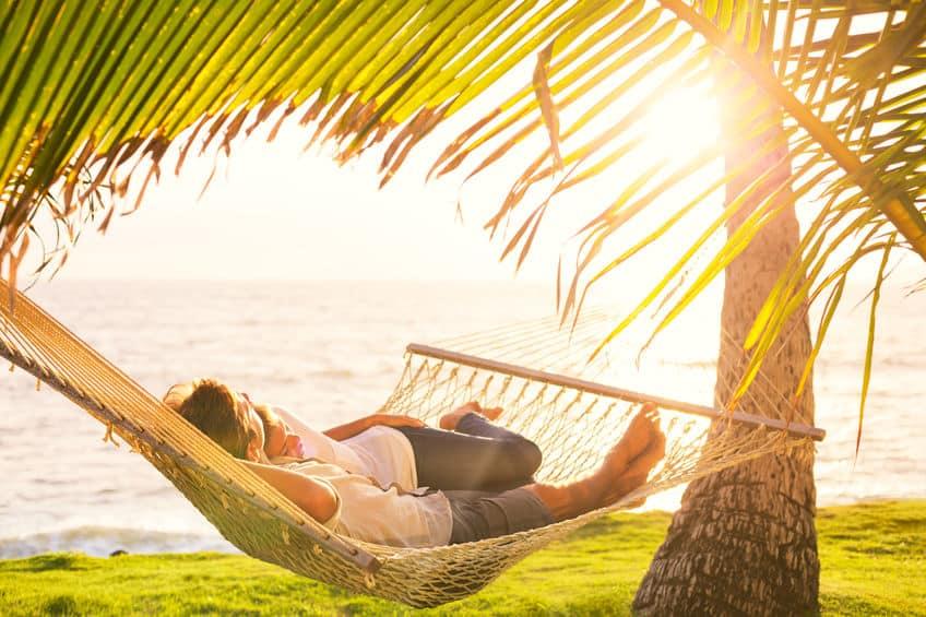 Casal deitado em uma rede de descanso em uma tarde de sol.