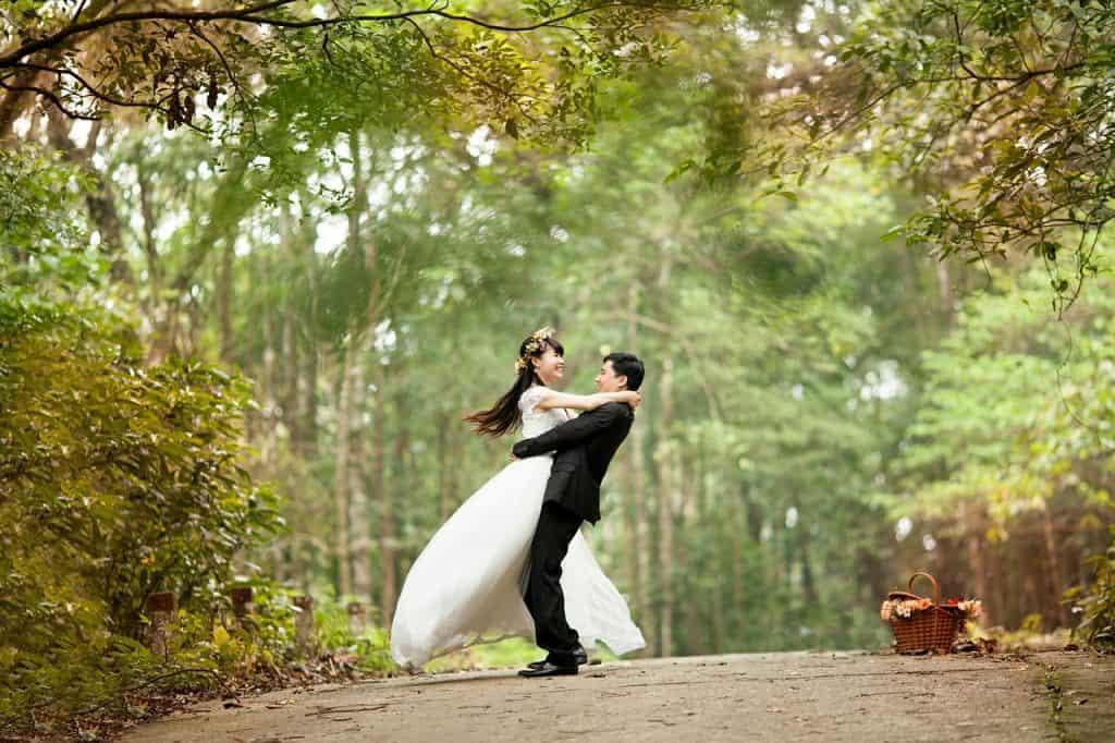 Na foto um casal de noivos abraçados e felizes em uma estrada de terra cercada por árvores.