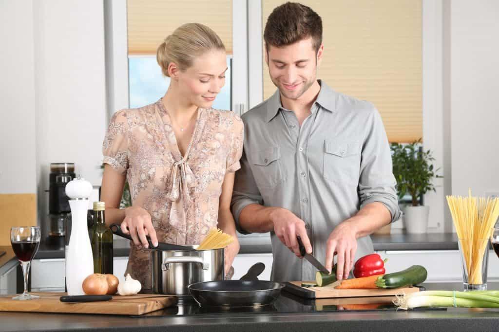 Foto de um casal atrás de uma bancada cozinhando. Ela segura uma colher dentro de uma panela com macarrão, e ele corta legumes. Em cima da bancada há também uma frigideira, tábuas, outros legumes, temperos e uma taça de vinho.