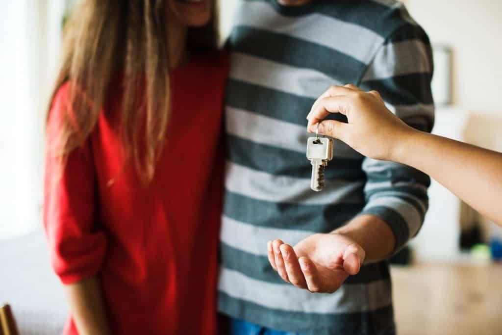 Na foto aparece um casal ao fundo com uma mão entregando as chaves de uma casa.