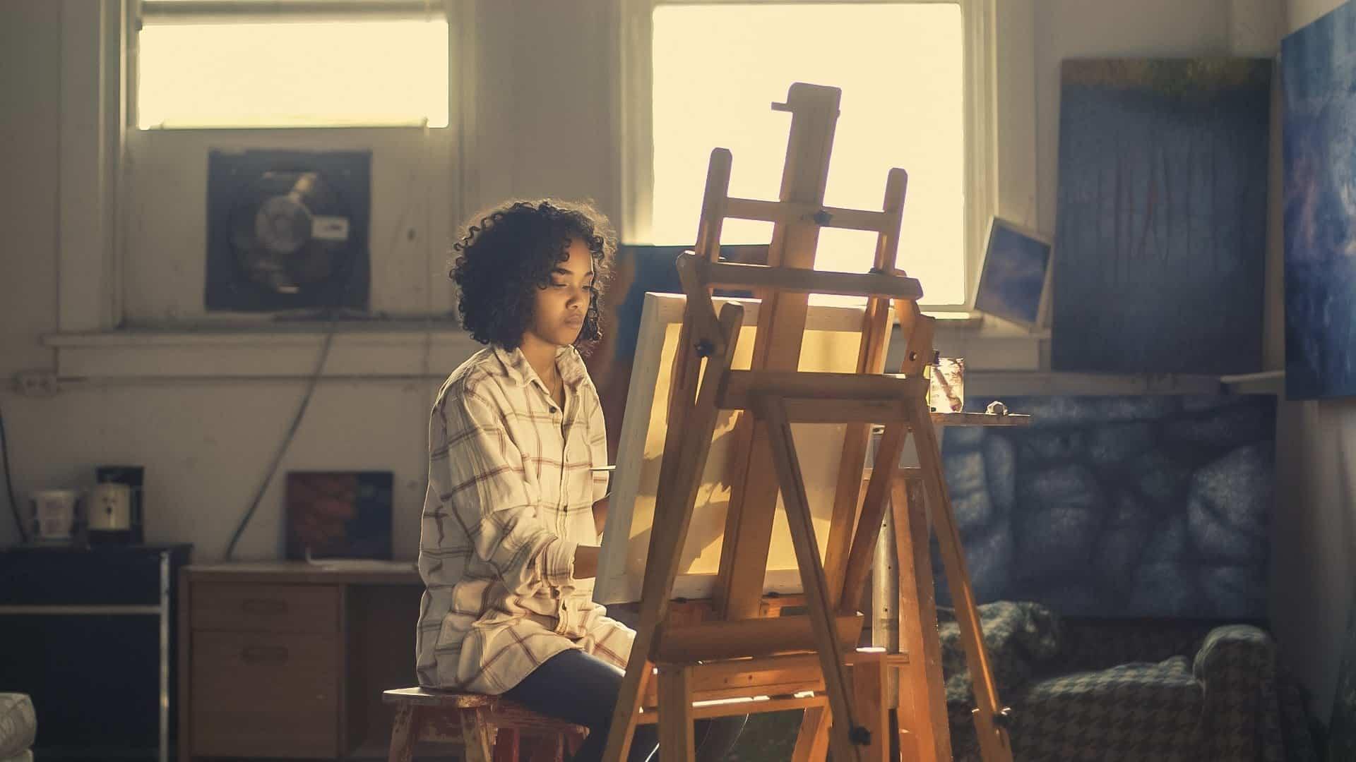 Mulher em uma sala. Ela está sentada de frente para um cavalete, pintando uma tela.