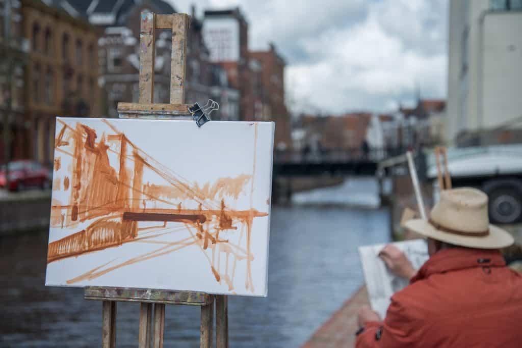 Imagem de cavaletes com artistas pintando paisagem de construções e canal.