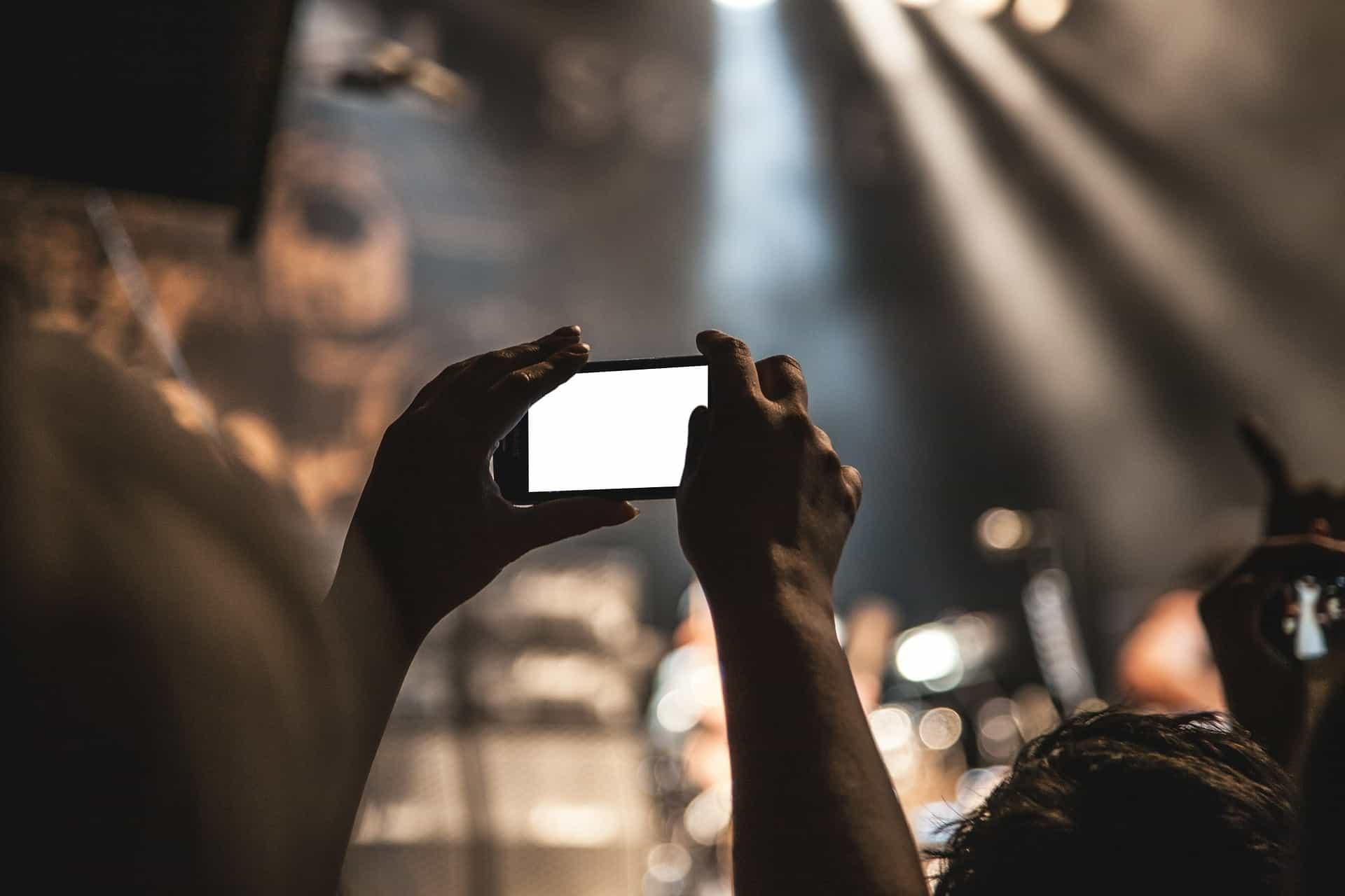 Fotografia de um celular sendo utilizado durante um show, para bater uma selfie. O visor branco indica o uso de flash para clareamento da foto.