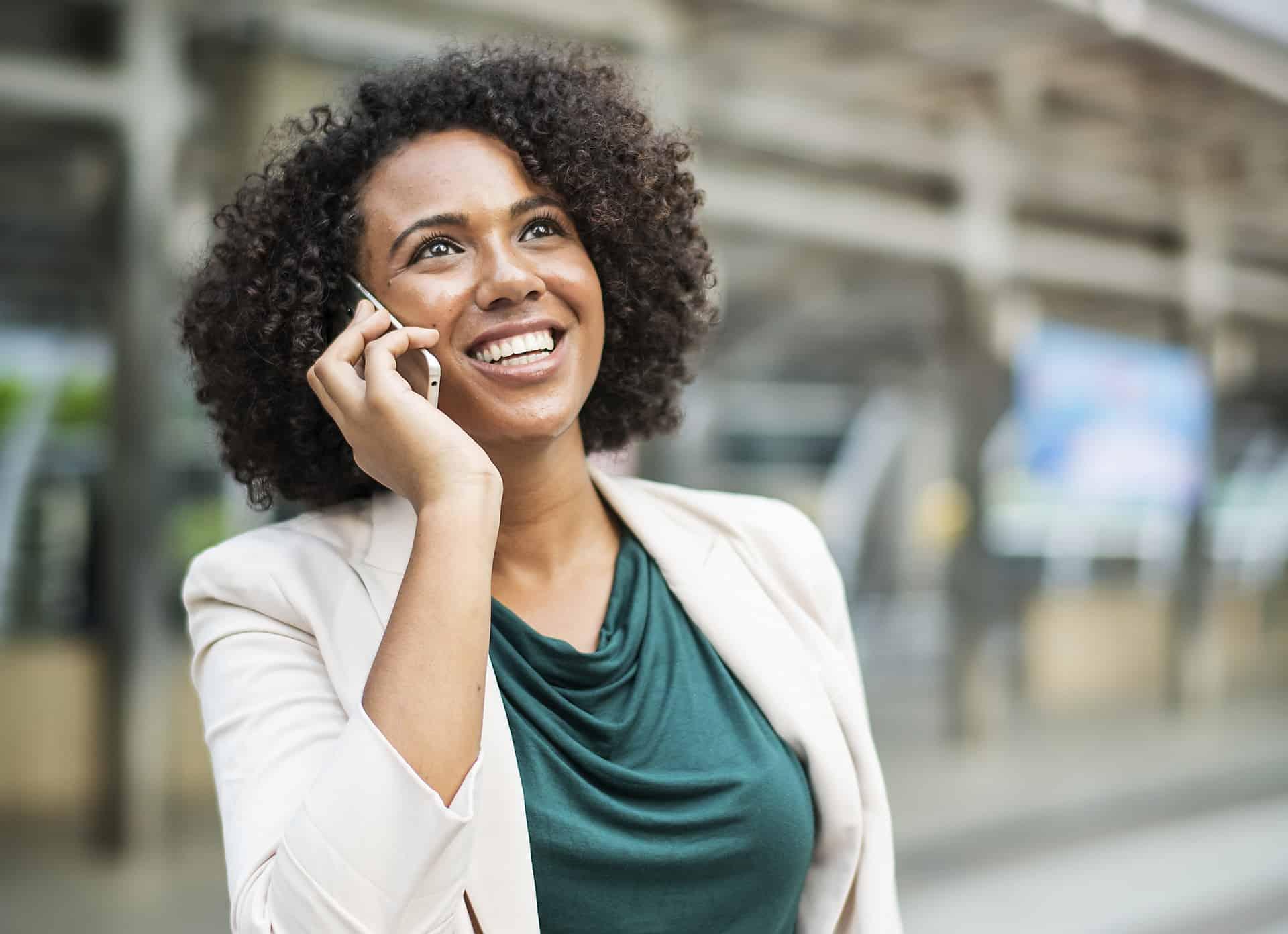 Uma mulher falando no celular, sorrindo e olhando para o alto.