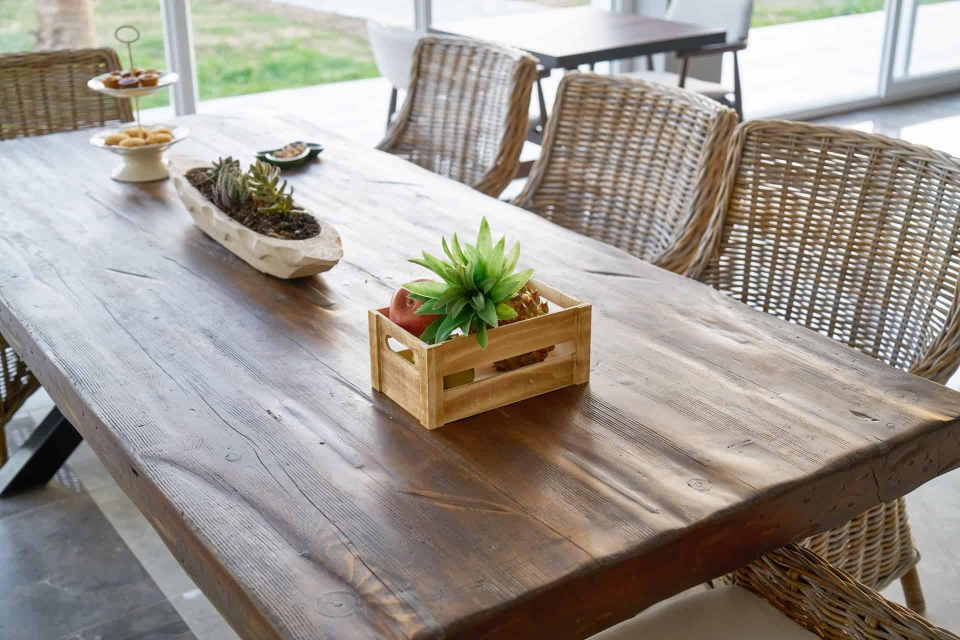 Foto de uma mesa grande de madeira, com quatro cadeiras de fibra bem rústicas. Em cima da mesa, um centro de mesa, e alguns alimentos em pratos e caixinhas.