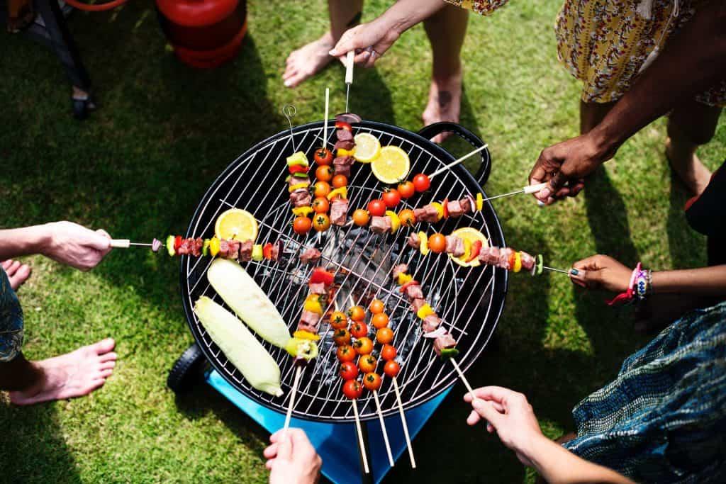 Foto de uma churrasqueira portátil, com várias pessoas ao redor colocando espetinhos de legumes e carne para grelhar.