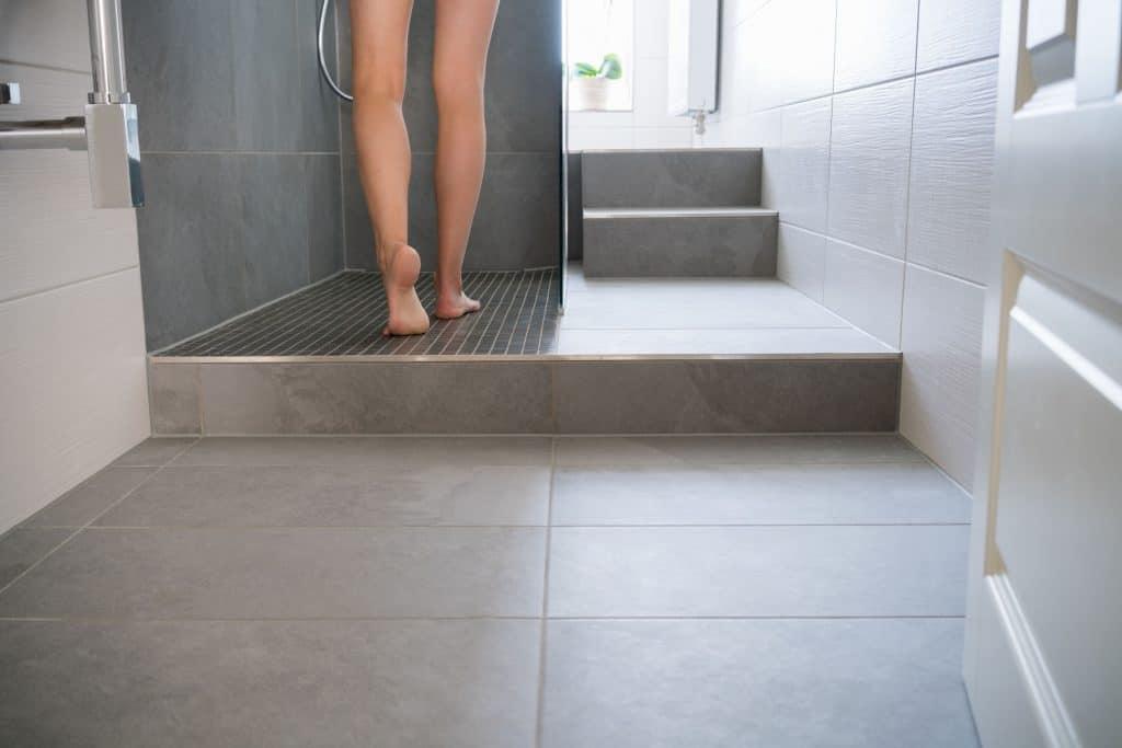 Imagem das pernas de uma mulher entrando no box do banheiro para tomar banho.