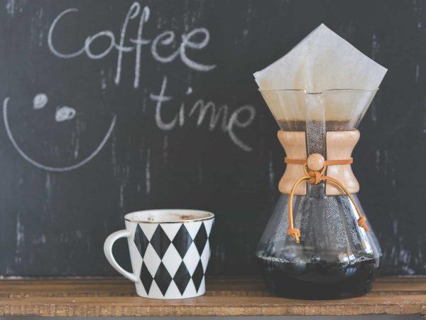 """Coador de café em vidro com filtro de papel ao lado de caneca de café com frase """"Coffee Time"""" desenhada em giz ao fundo."""