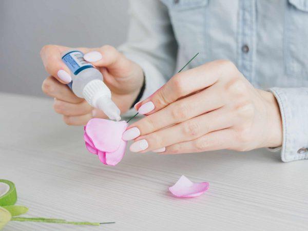 A imagem mostra mão de mulher colando pétalas de flor artificial com cola para tecido.