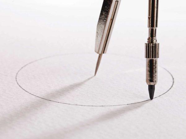 Na foto estão as pontas de um compasso desenhando um círculo.