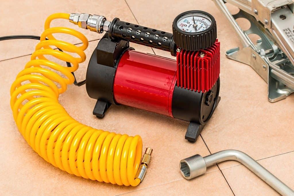 Compressor em repouso, com mangueira engatada, mas sem acessórios para utilização (pistola de ar, ponta). Nas laterais da foto, uma chave de boca e um macaco hidráulico.
