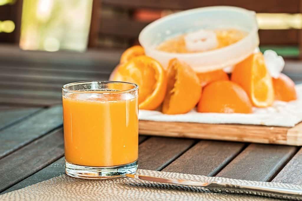 Copo com suco de laranja em primeiro plano sobre mesa de tábua de madeira e laranjas cortadas espremidas com espremedor manual ao fundo.