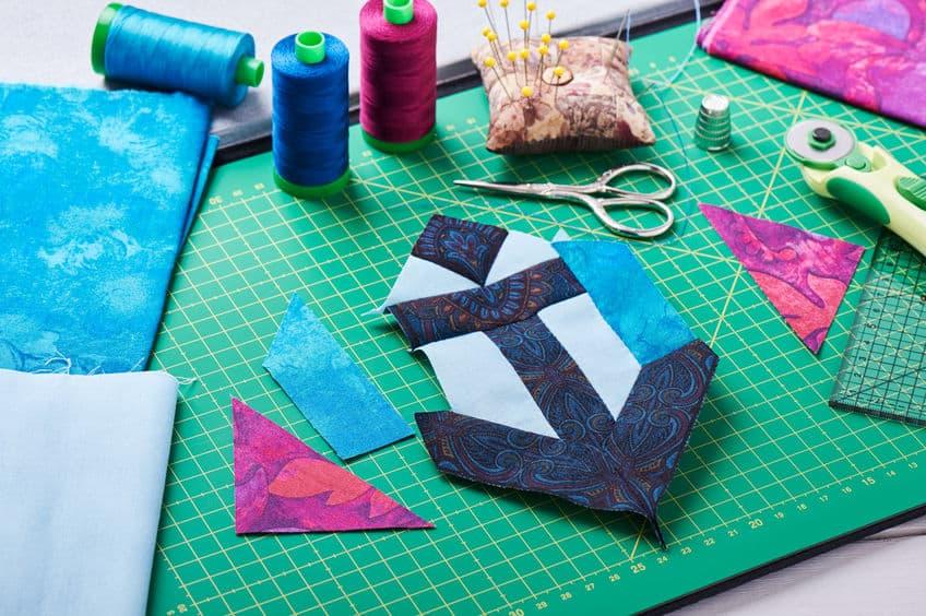 Base de corte com tecidos, linha, tesoura e outros itens sobre ela.