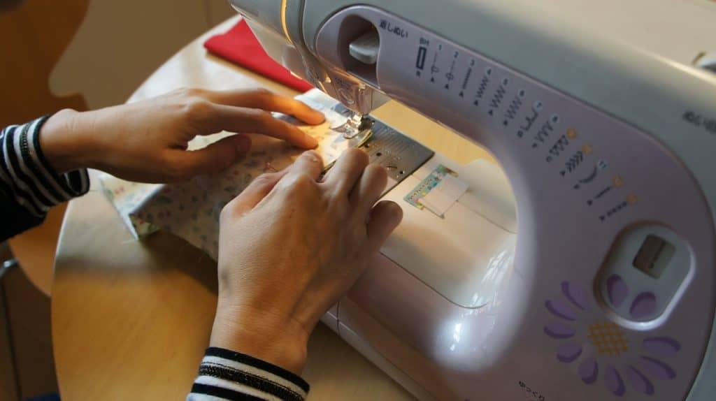 Mão de mulher costurando em máquina de costura portátil.