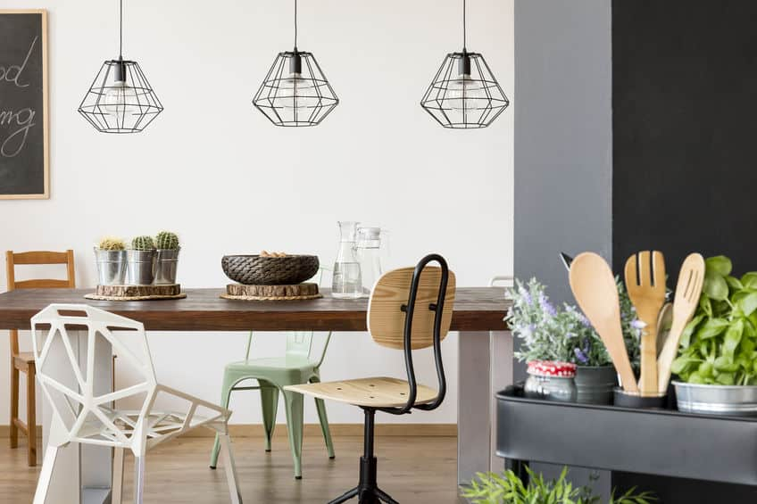 Foto de uma sala de jantar com decoração moderna, com quatro cadeiras diferentes ao redor da mesa.