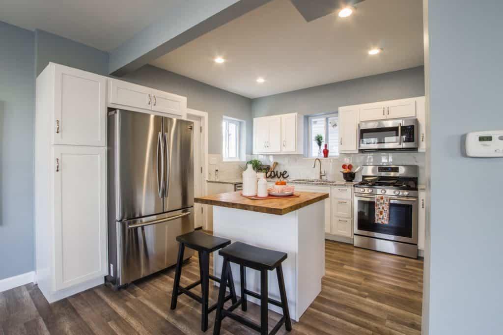 Na foto está uma cozinha com chão de madeira, uma ilha no meio, paredes azuis e armários brancos.