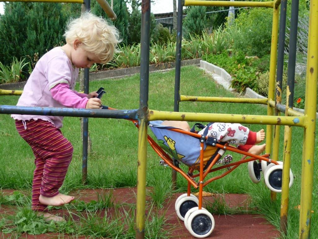 Criança brincando com carrinho de boneca.