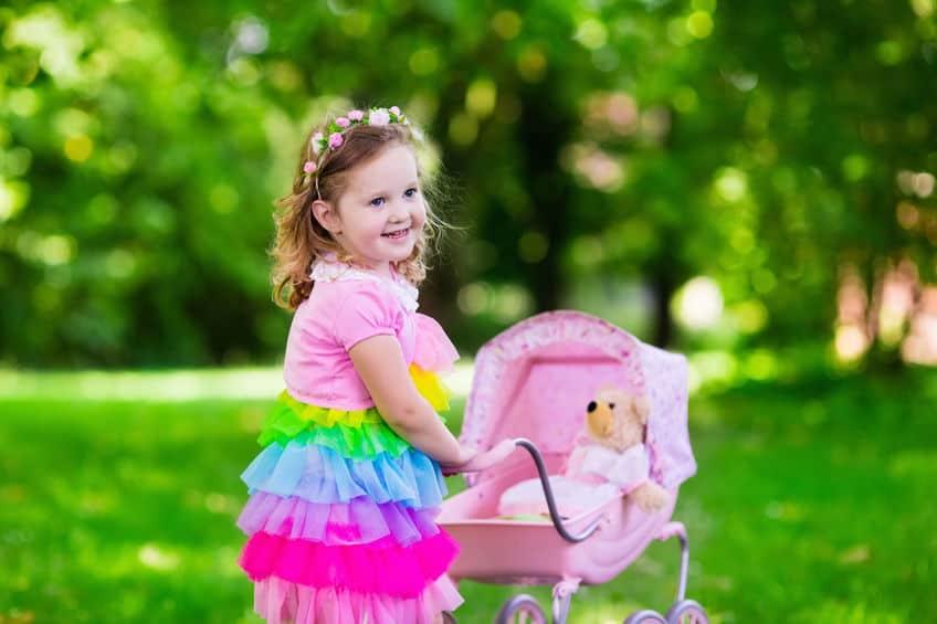 Imagem de criança brincando com carrinho.