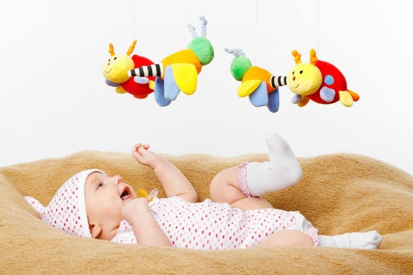 Bebê deitado com móbile colorido sobre ele.