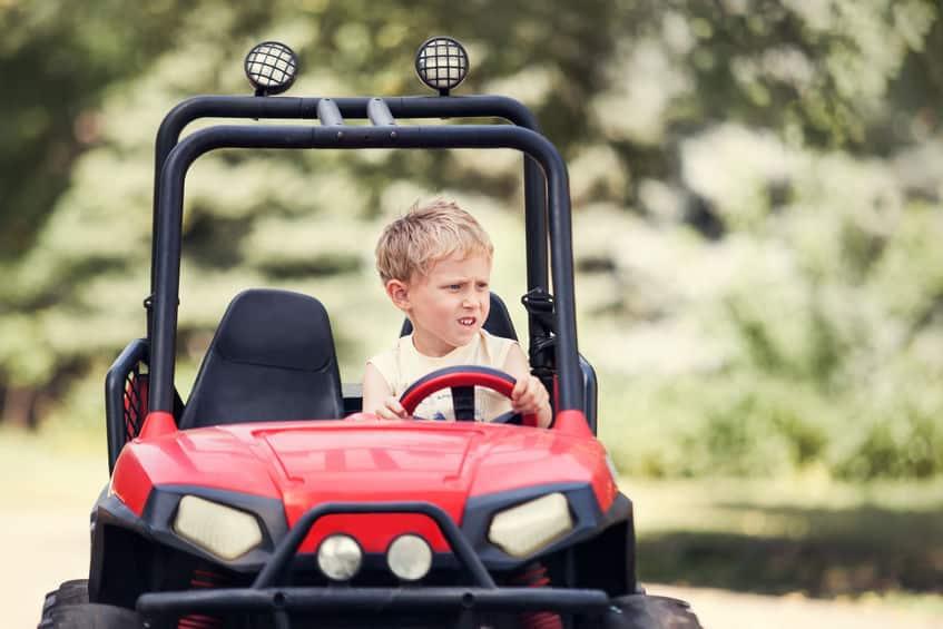 Criança pilotando um quadriciclo infantil vermelho.