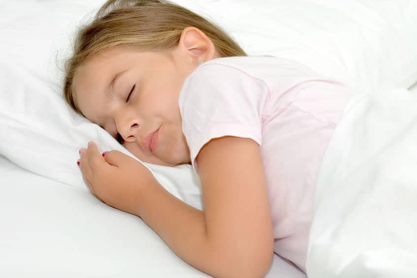 Imagem mostra menina dormindo de bruço.