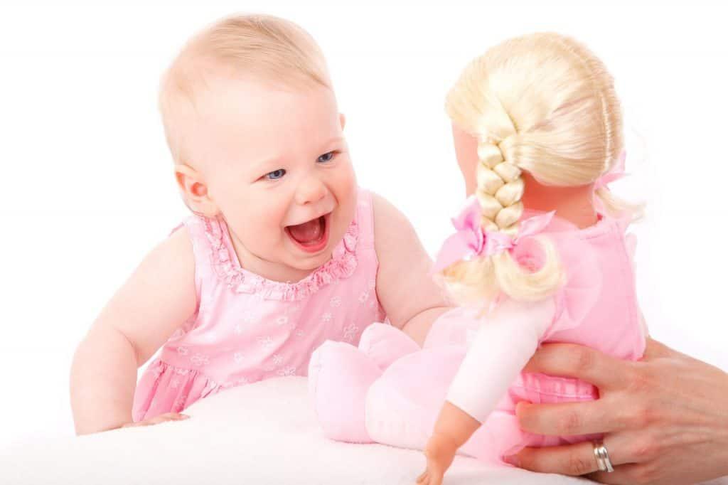 Bebê sorrindo ao ver uma boneca na sua frente.
