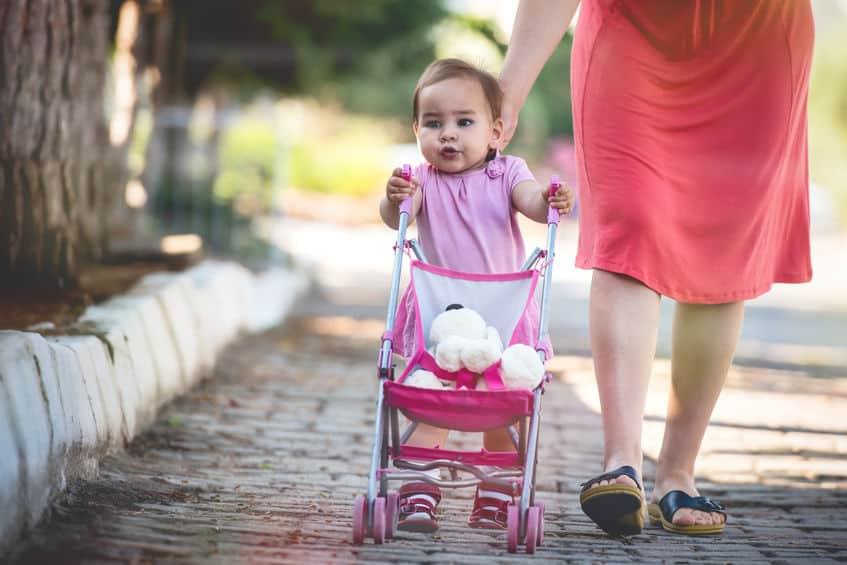 Mãe e criança com carrinho de boneca.