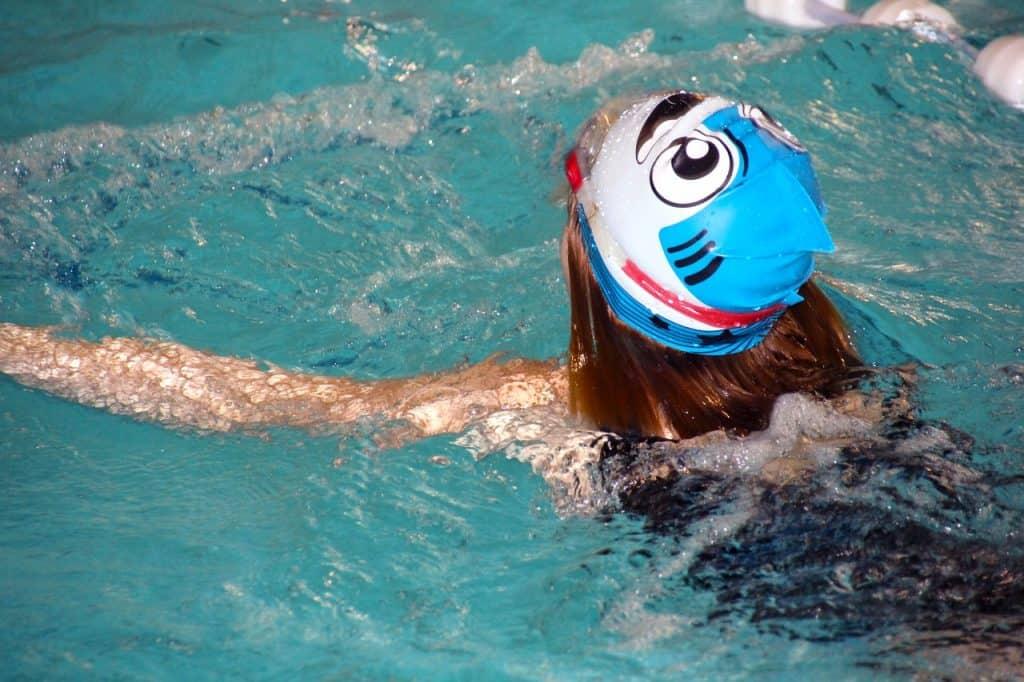 Imagem de uma criança de costas na piscina com touca de natação estampada de tubarão.