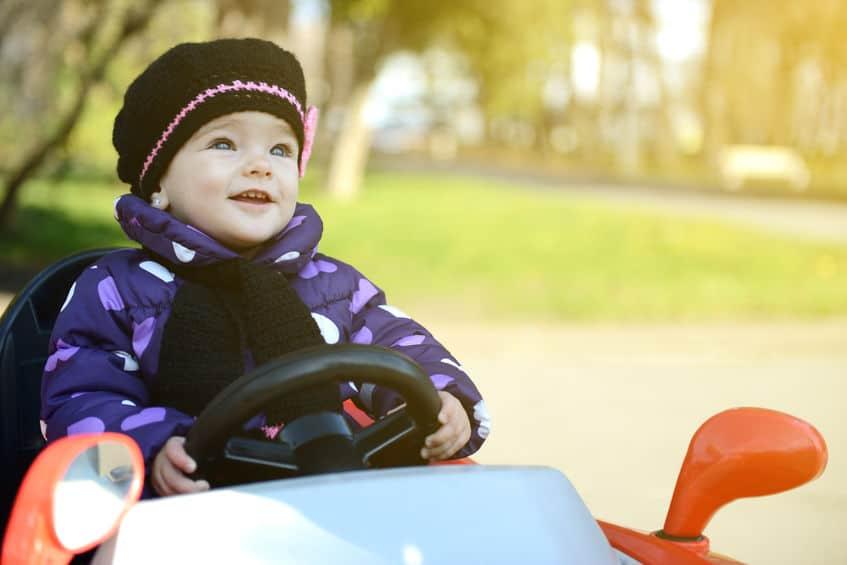 Bebê na direção de um quadriciclo infantil.