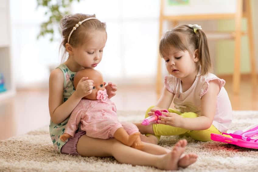 Imagem de duas meninas sentadas no chão brincando com boneca.