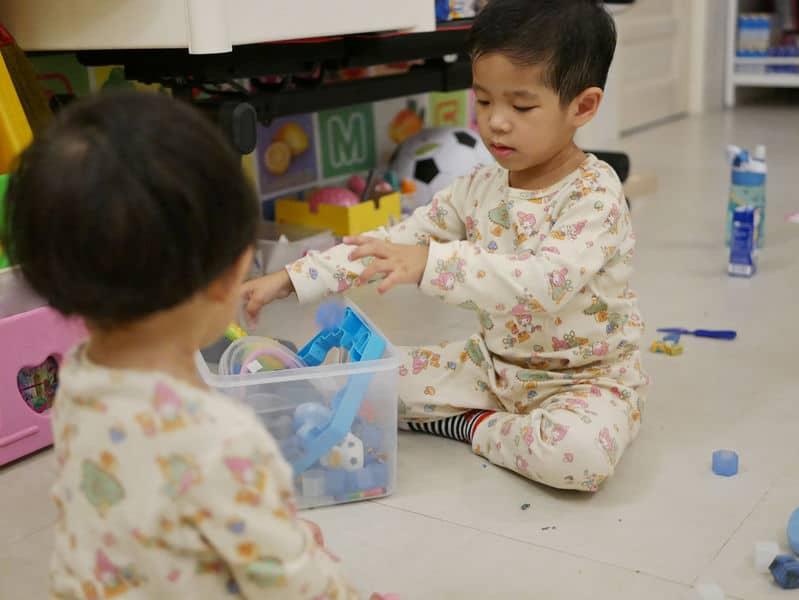 Dois garotos guardando brinquedos em caixa.