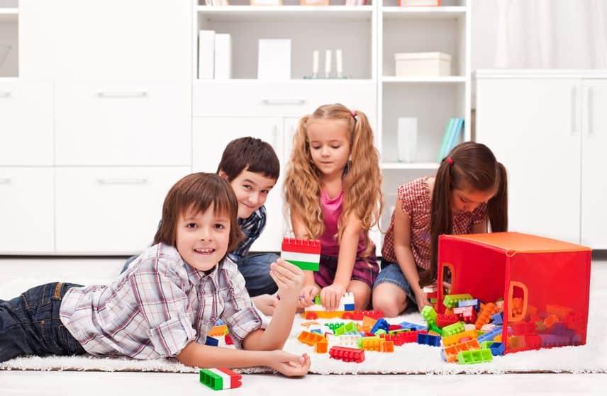 Crianças brincando com blocos de montar no tapete.