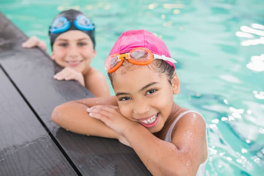 Imagem de duas crianças em piscina usando touca e óculos de natação.