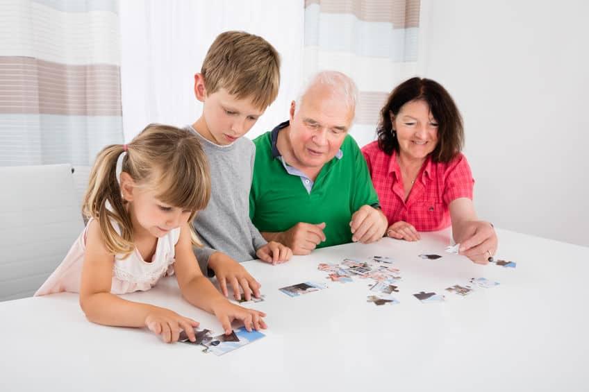 Imagem de crianças e adultos jogando quebra cabeça.