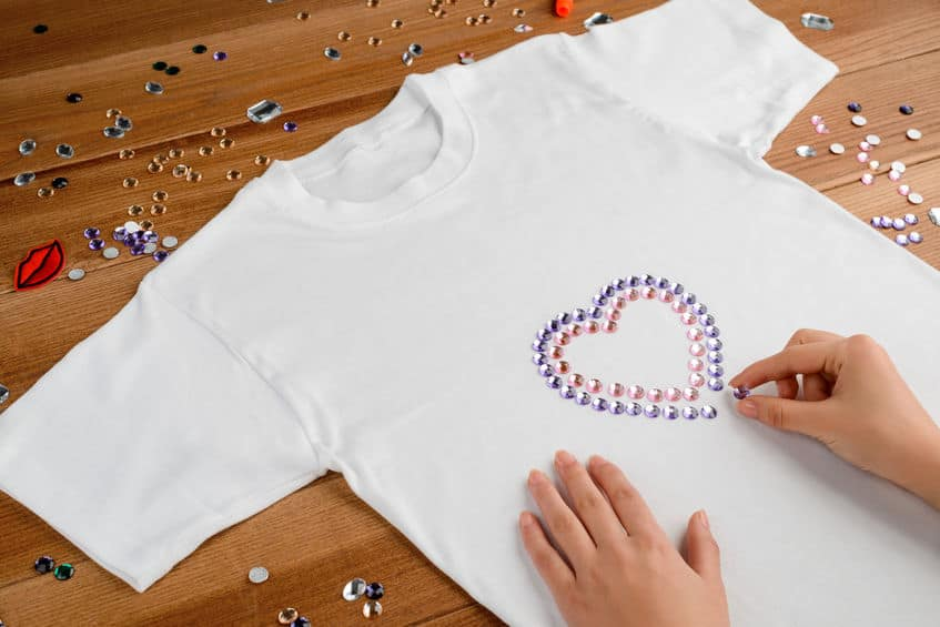Mão customizando camiseta branca com pedras.