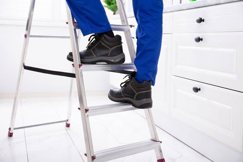 Pés de homem subindo em uma escada dobrável de alumínio.