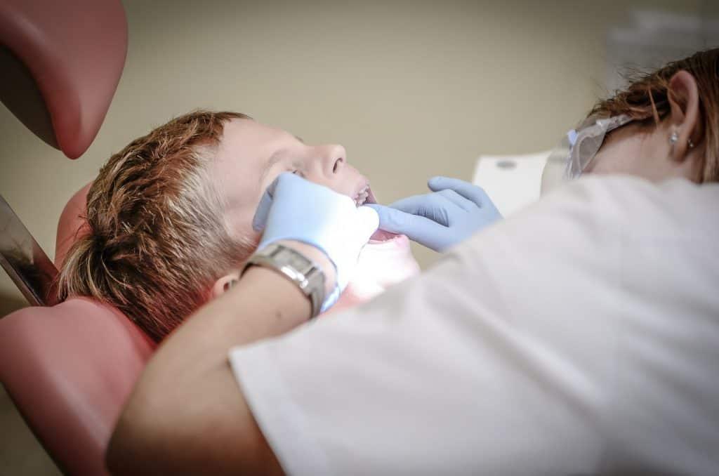 Uma dentista tratando os dentes de uma criança.