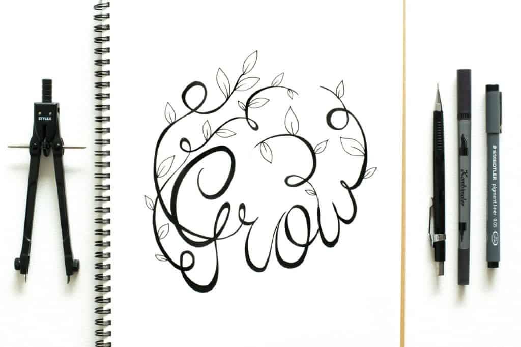 """Na foto um caderno com a palavra """"Grow"""" escrita com um compasso do lado esquerdo e duas canetas e uma lapiseira do lado direito."""