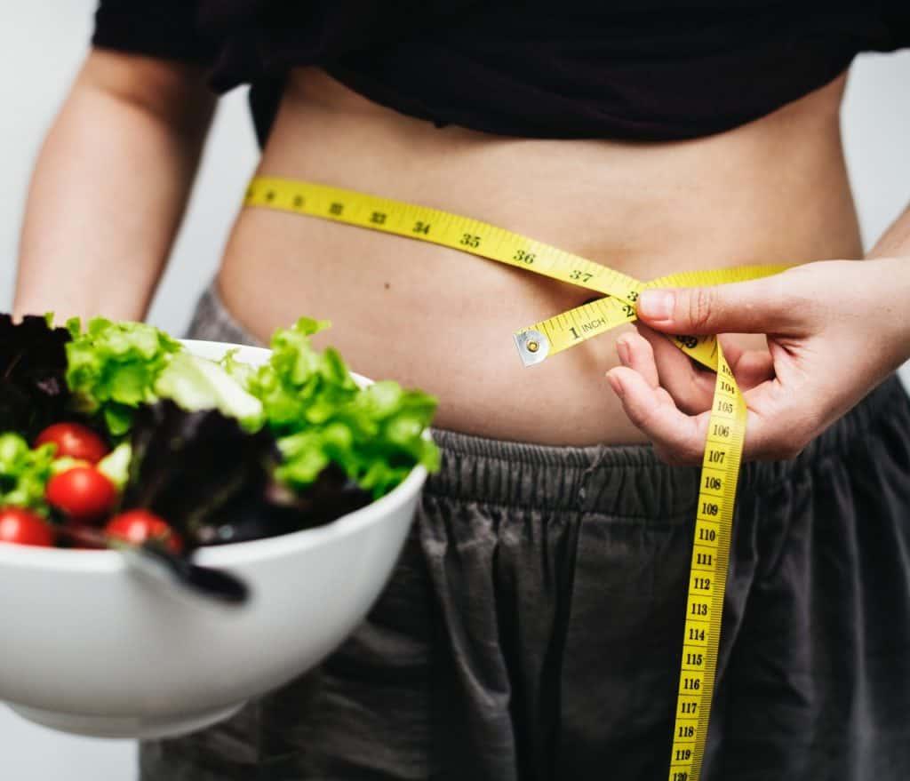 Mulher medindo com fita métrica e barriga, segurando prato de salada.