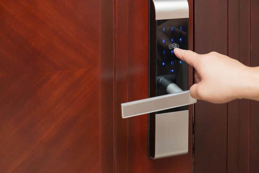 Dedo digitando senha em porta com fechadura digital.