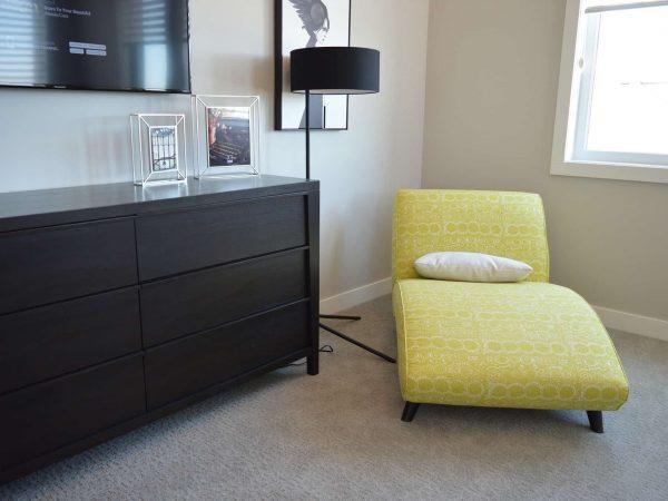 Foto de uma chaise longue amarela, com uma almofada branca em cima, em um ambiente com estante preta com porta retratos, luminária, TV e quadro na parede.