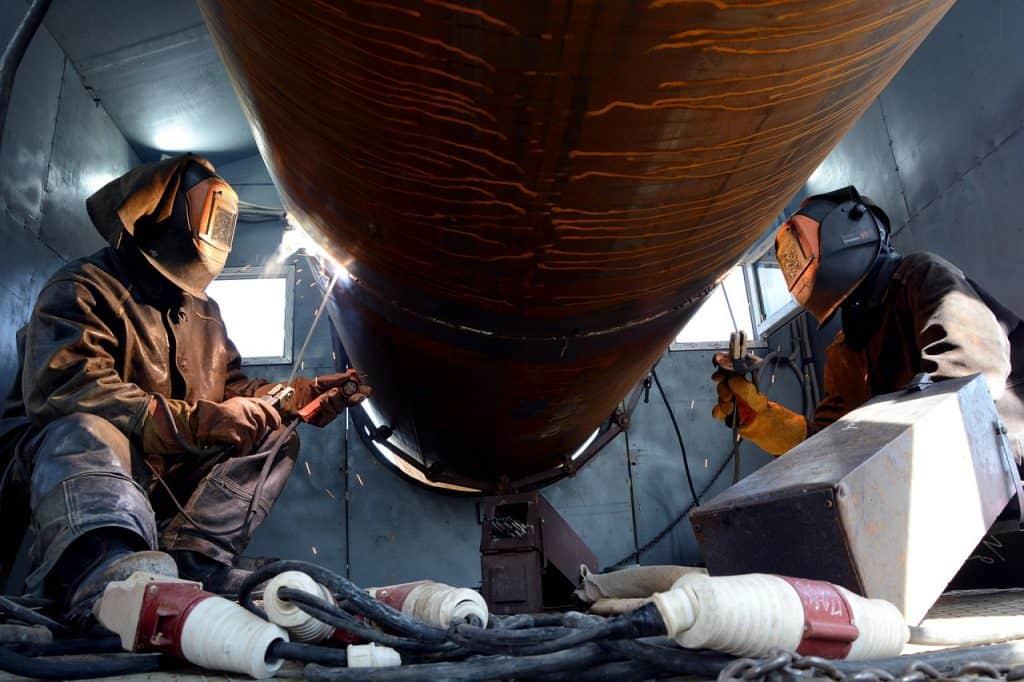 Imagem de dois homens fazendo solda em tambor.