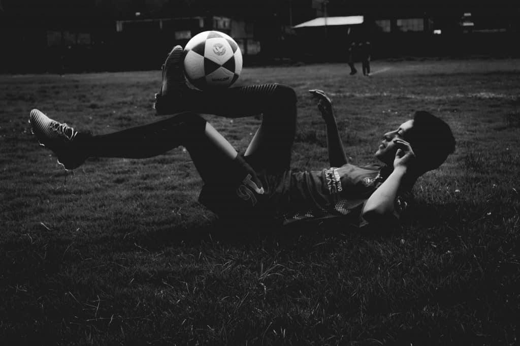 Imagem mostra um jogador deitado no chão, controlando a bola entre seu pé direito e sua canela.