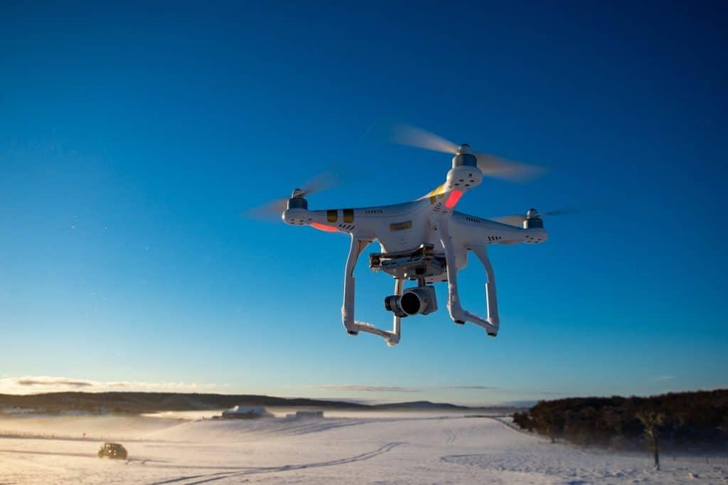 Imagem de um drone sobrevoando uma área coberta de neve.