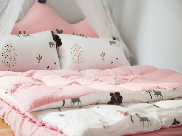 Close up image of girl's bed with matching duvet with pillowcases and sheet.