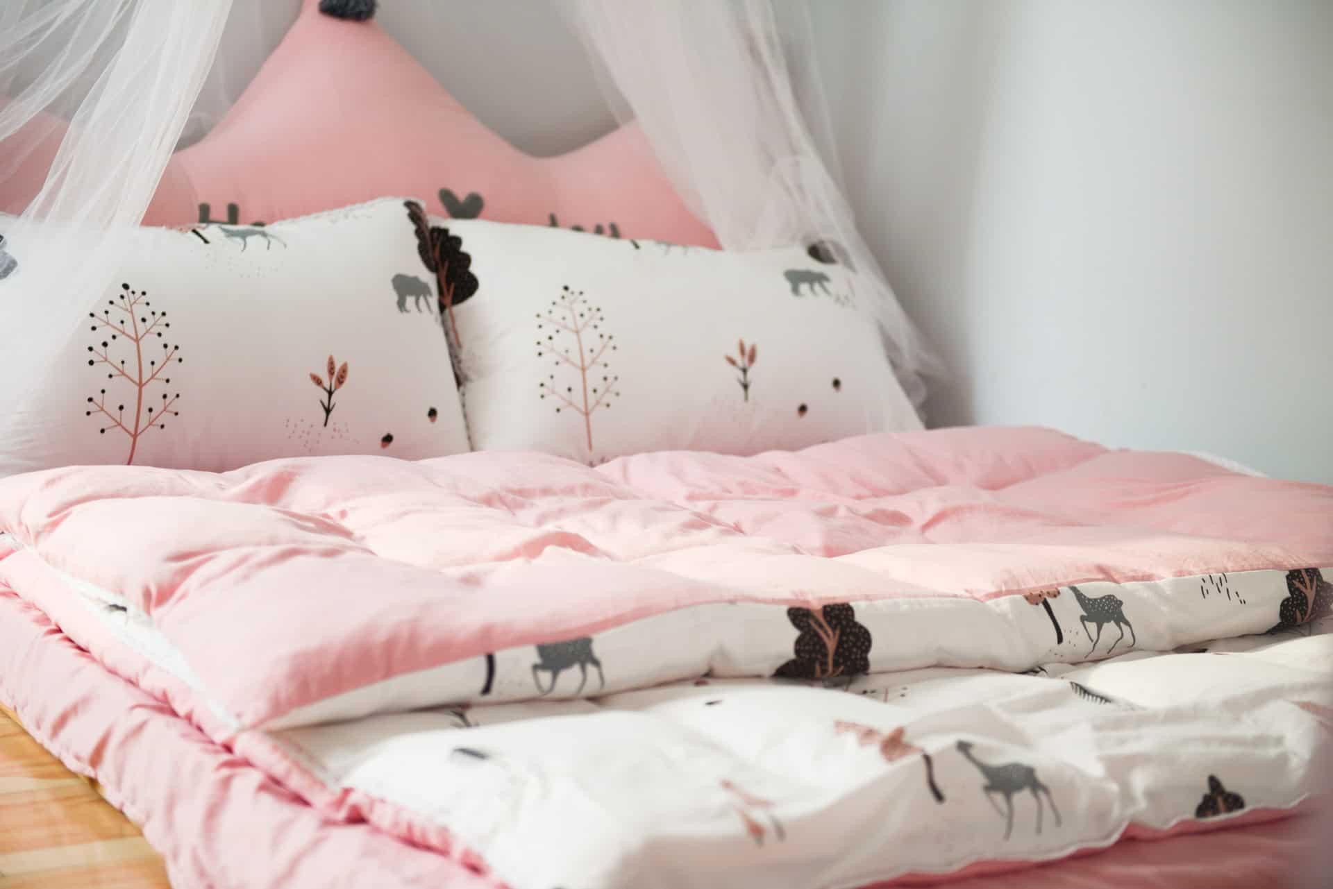 Imagem aproximada de cama de menina com edredom combinando com fronhas e lençol.