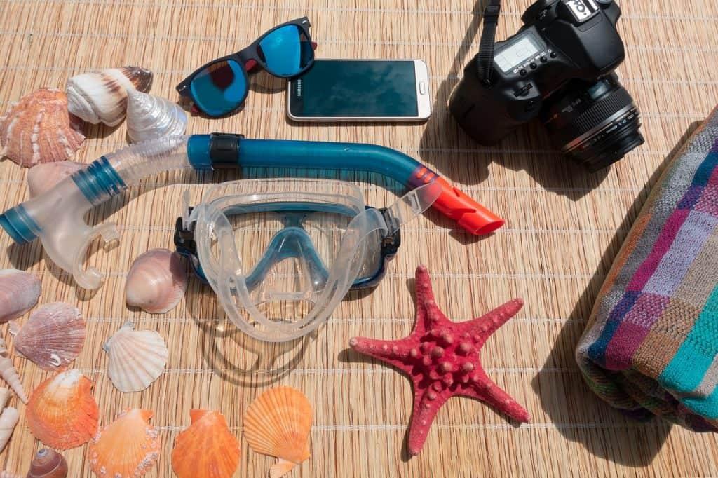 Na foto equipamentos de mergulho, câmera digital, celular e conchas e estrela do mar em uma esteira de bambu.