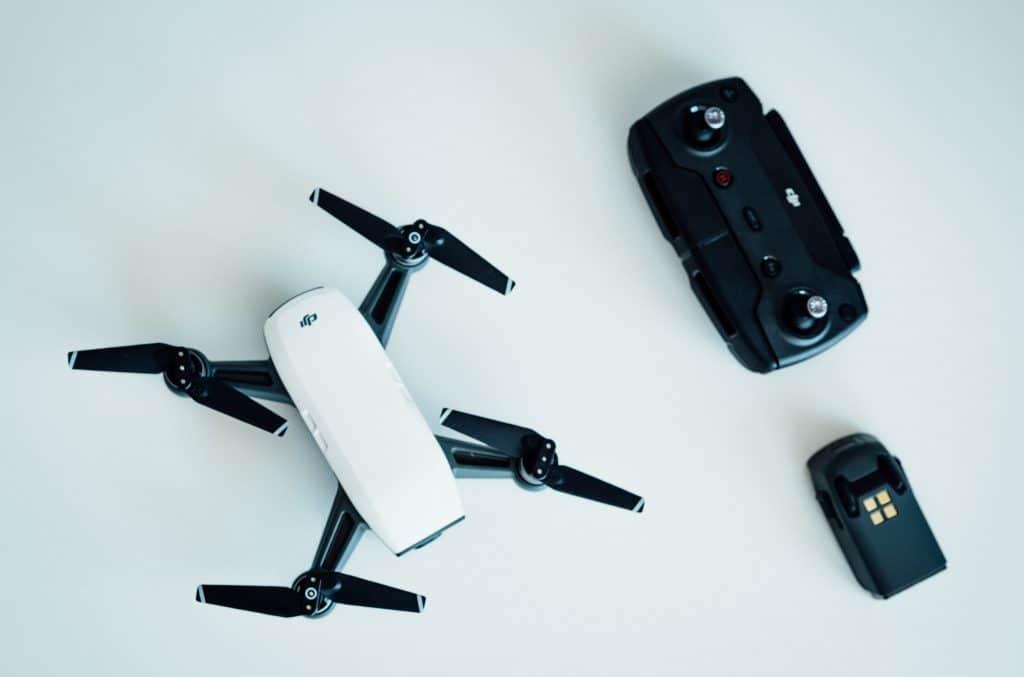 Imagem de um drone, controle remoto e bateria.