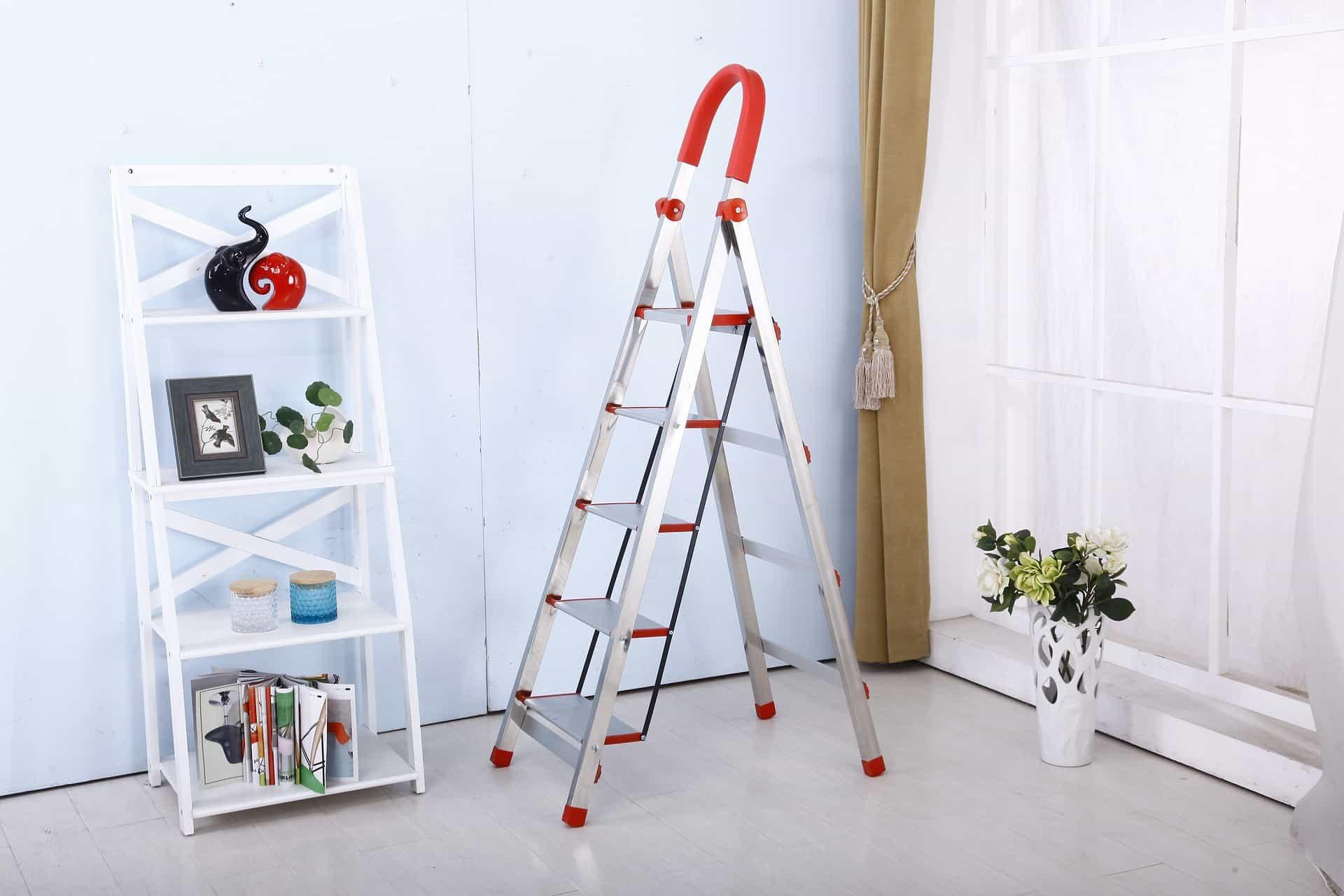 Uma escada dobrável de alumínio em uma sala com uma estante, uma cortina e um vaso com flores.