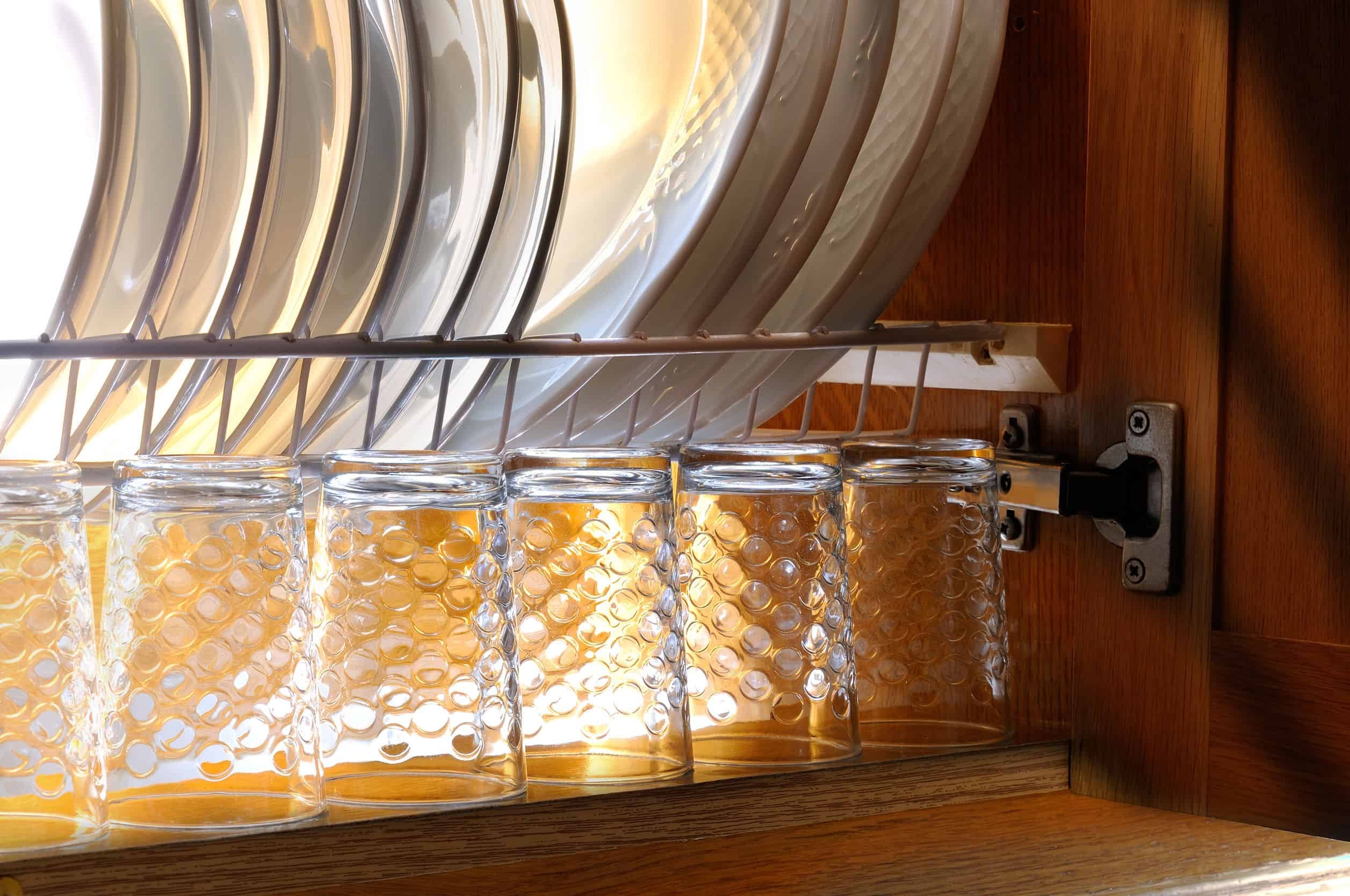 Escorredor de pratos e copos dentro do armário.